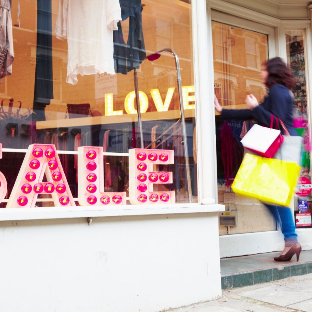 A young lady with shopping bags enters a boutique that is advertising special offers.